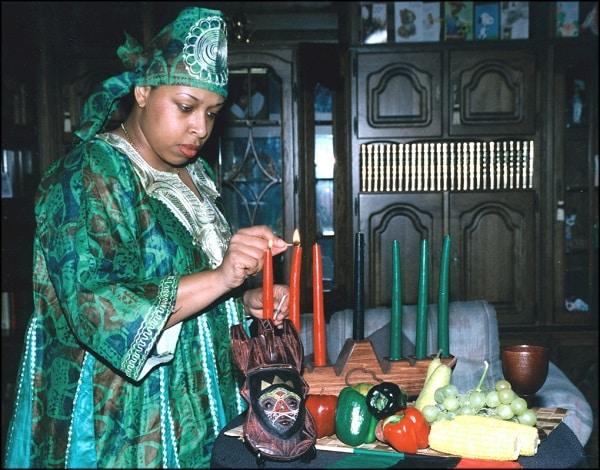 woman lighting candle for kwanzaa
