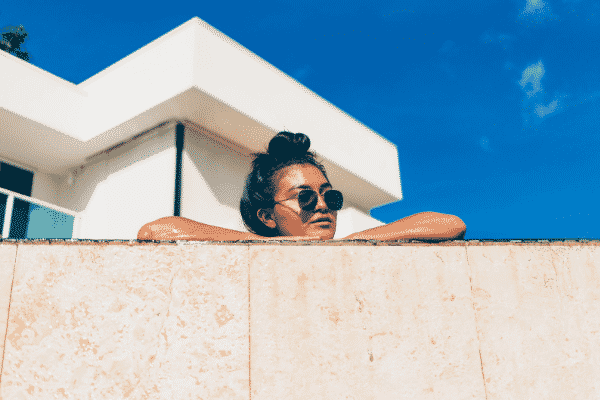 woman in the un looking over a wall, summer skin care