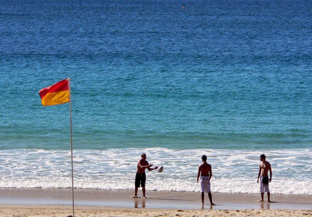 tips on how to stay water safe at Australian beaches this summer. Photo of friends playing with a ball on a beach.
