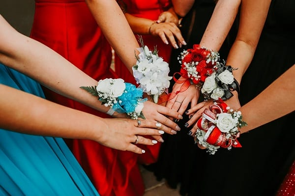 Year 12 formals being canceleld reflects poorly on education system. A group of girls with corsages putting their hands together in a circle.