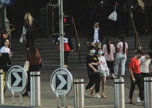People walking outside a Melbourne train station.