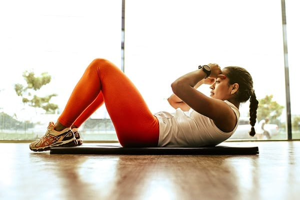 A woman is doing crunches as part of her workout