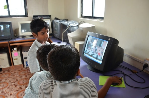 Gyanankur students operating an old model of a computer