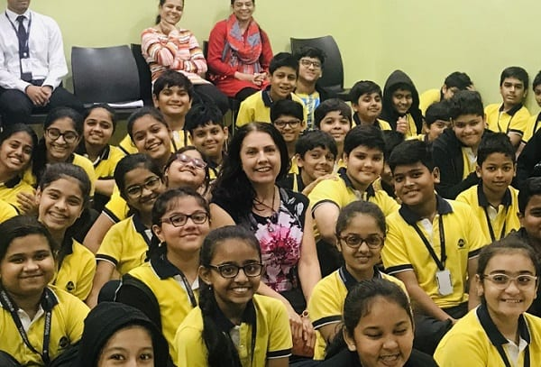 Margaret teaching at Universal School in Tardeo, Mumbai. She is pictured her surrounded by young students from the school.