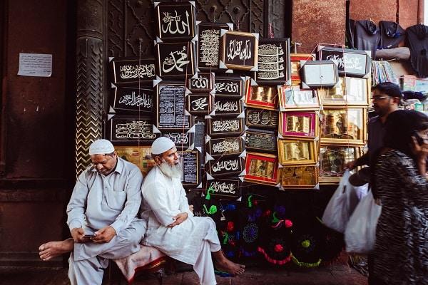 Muslim men sit outside the Jama Masjid in Delhi, India