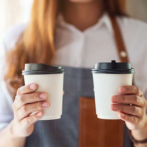 A waitress holding and serving two paper cups of hot coffee in cafe