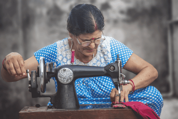 Migrants, especially those from poor backgrounds, will often fix or repurpose an item rather than dispose of it. Indian Woman sewing