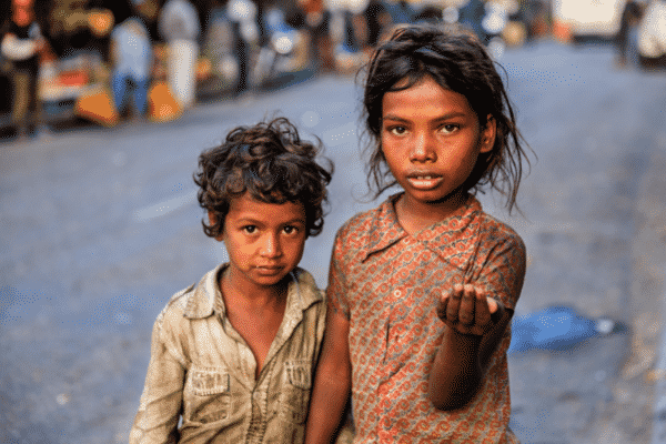two poor indian children stand on the street