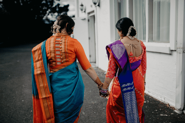 Two indian women dressed in vibrant sarees have their back towards the camera and walk hand in hand. Hindu same sex wedding