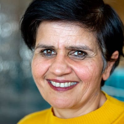 portrait of South Asian woman smiling with cropped black hair wearing yellow sweater